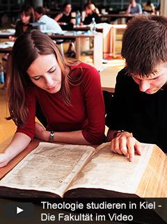 Studierende mit einer Bibel aus dem 17. Jhd. im Freihandbereich der Universitätsbibliothek